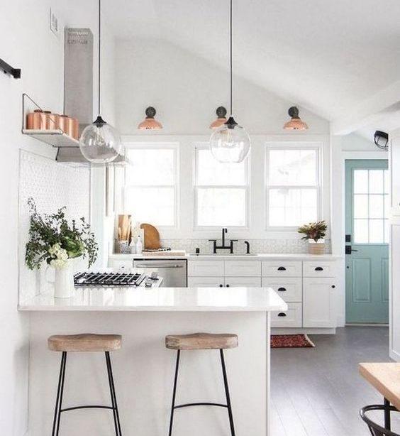 Farmhouse Modern Style All White Küche mit geschnitzten Küchenhockern aus Holz und Kristallpendelleuchten